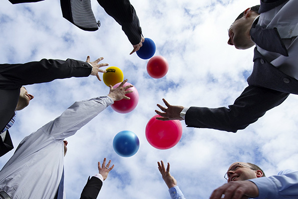 Low angle view of businesspeople throwing balls